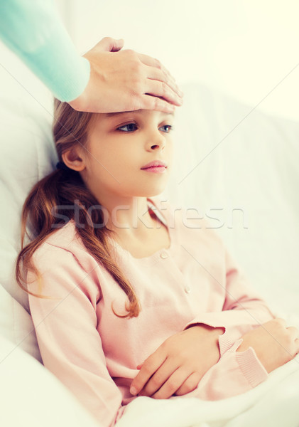ill girl child with thermometer and caring mother Stock photo © dolgachov