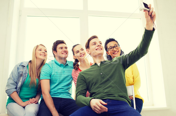five smiling students taking picture with camera Stock photo © dolgachov