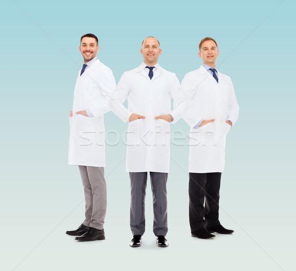 smiling male doctors in white coats Stock photo © dolgachov