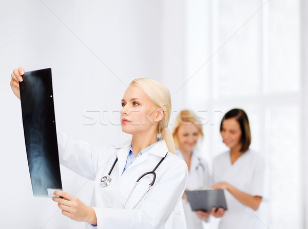 serious female doctor looking at x-ray Stock photo © dolgachov
