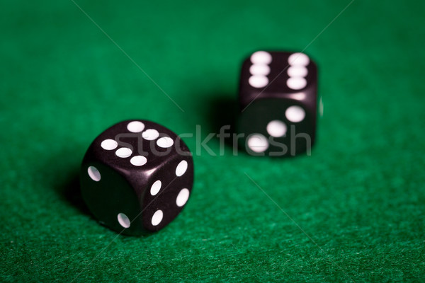 close up of black dice on green casino table Stock photo © dolgachov
