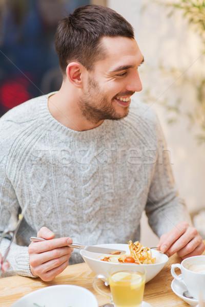 happy young man having dinner at restaurant Stock photo © dolgachov