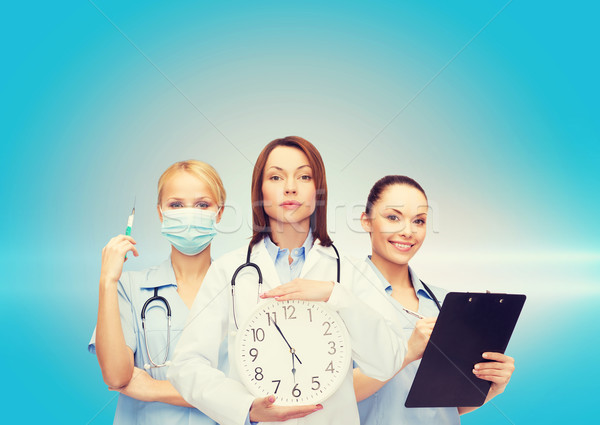 calm female doctor and nurses with wall clock Stock photo © dolgachov