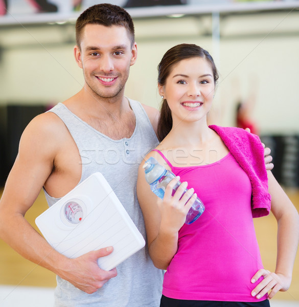 two smiling people with scale in the gym Stock photo © dolgachov