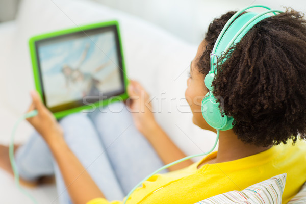 happy african woman with tablet pc and headphones Stock photo © dolgachov