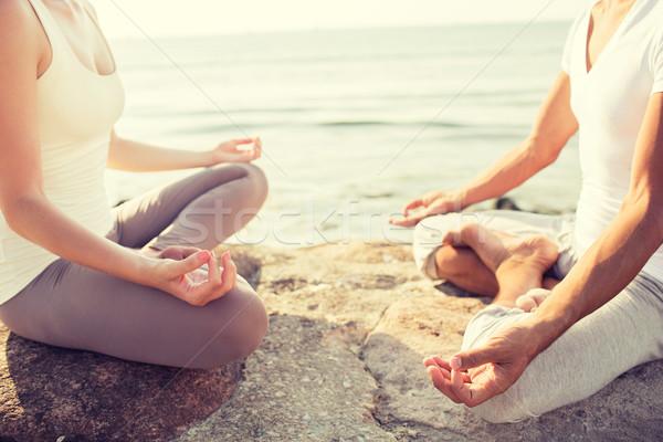 Stock photo: close up of couple making yoga exercises outdoors