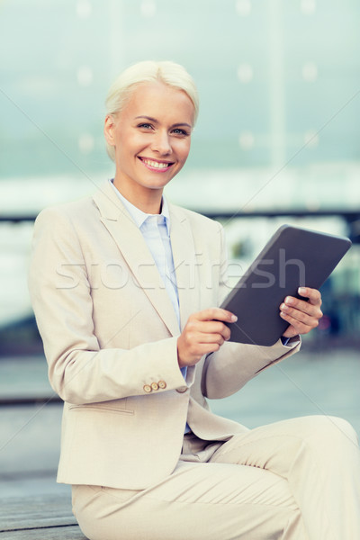 smiling businesswoman with tablet pc outdoors Stock photo © dolgachov