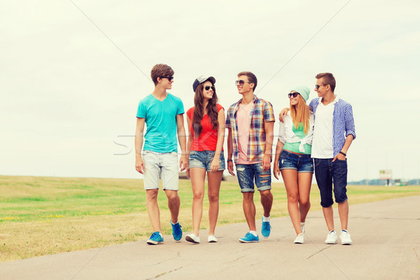 group of smiling teenagers walking outdoors Stock photo © dolgachov