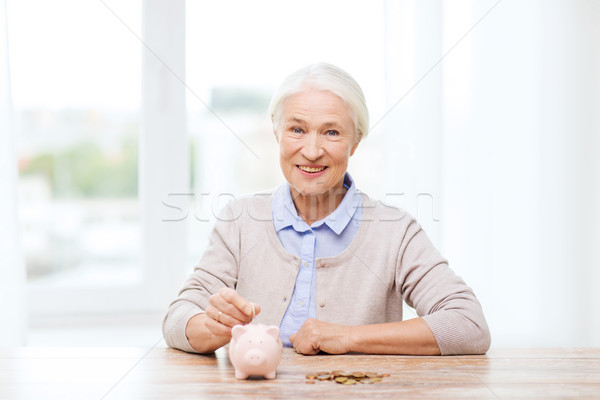 Stock photo: senior woman putting money to piggy bank at home