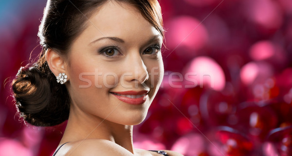 happy woman with diamond earring over red lights Stock photo © dolgachov