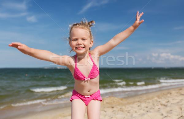 happy little girl in swimwear having fun on beach Stock photo © dolgachov