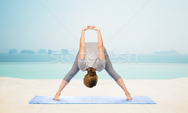 woman making yoga wide-legged forward bend on mat Stock photo © dolgachov