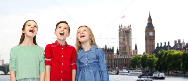 amazed boy and girls looking up over london Stock photo © dolgachov