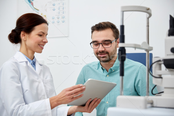 optician with tablet pc and patient at eye clinic Stock photo © dolgachov