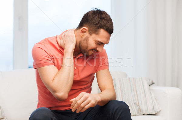 unhappy man suffering from neck pain at home Stock photo © dolgachov
