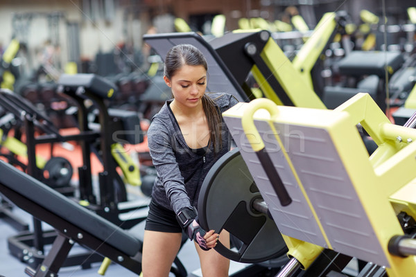 young woman adjusting leg press machine in gym Stock photo © dolgachov