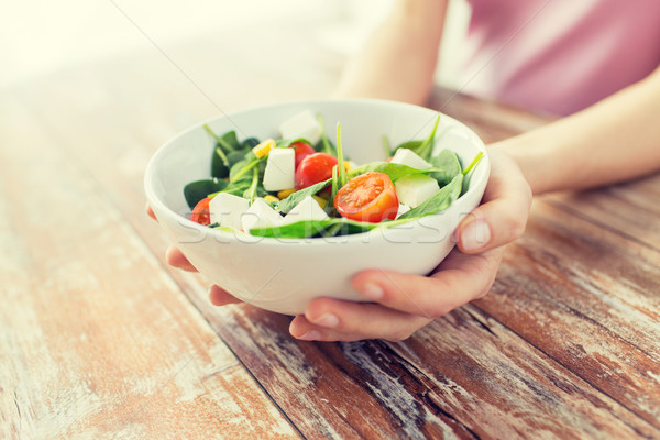 close up of young woman hands showing salad bowl Stock photo © dolgachov