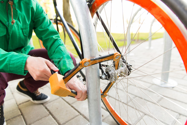 close up of man fastening bicycle lock on parking Stock photo © dolgachov