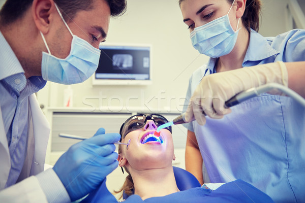dentists treating woman patient teeth at clinic Stock photo © dolgachov