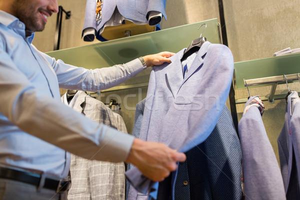 close up of man choosing jacket at clothing store Stock photo © dolgachov