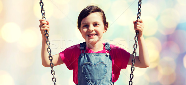 happy little girl swinging on swing over lights Stock photo © dolgachov