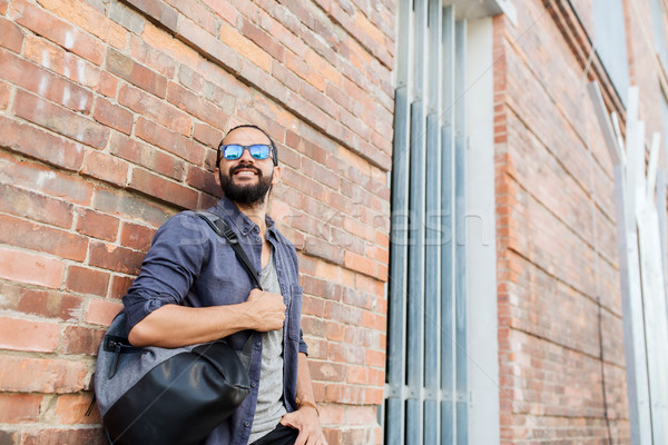 happy man with backpack standing at city street Stock photo © dolgachov