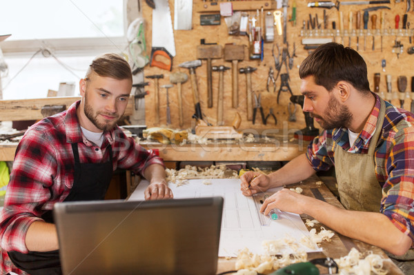 carpenters with laptop and blueprint at workshop Stock photo © dolgachov