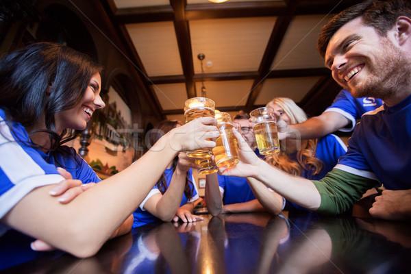 football fans clinking beer glasses at bar or pub Stock photo © dolgachov