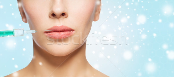 close up of woman face and syringe over snow Stock photo © dolgachov