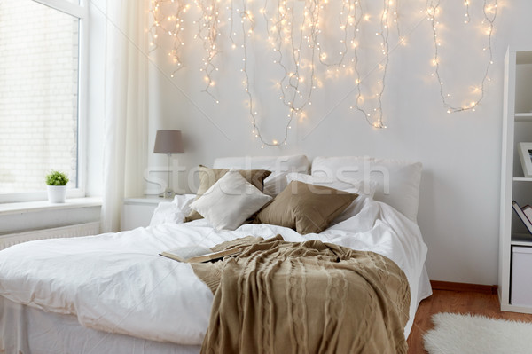 bedroom with bed and christmas garland at home Stock photo © dolgachov