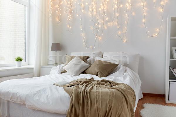 Hálószoba ágy karácsony girland otthon kényelem Stock fotó © dolgachov