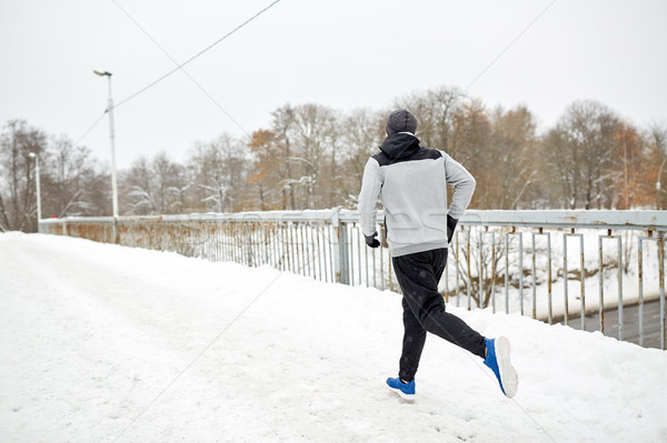 Stock photo: man running along snow covered winter bridge road