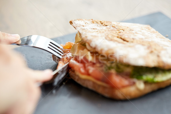 Stock photo: person eating salmon panini sandwich at restaurant