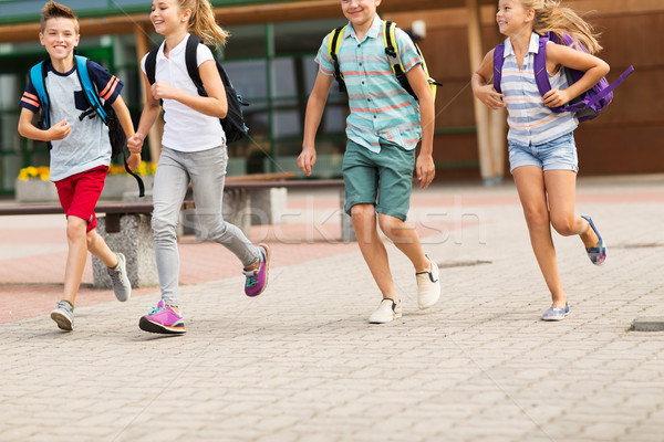 group of happy elementary school students running Stock photo © dolgachov