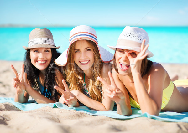 happy young women in bikinis on summer beach Stock photo © dolgachov