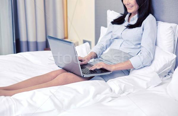 Mosolyog üzletasszony laptop gépel ágy üzleti út Stock fotó © dolgachov