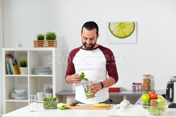 man with blender cup cooking food at home kitchen Stock photo © dolgachov