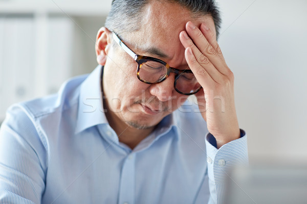 businessman suffering from headache at office Stock photo © dolgachov