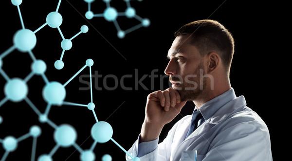 scientist looking at molecule projection Stock photo © dolgachov