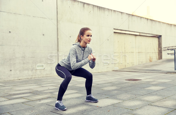 happy woman doing squats and exercising outdoors Stock photo © dolgachov