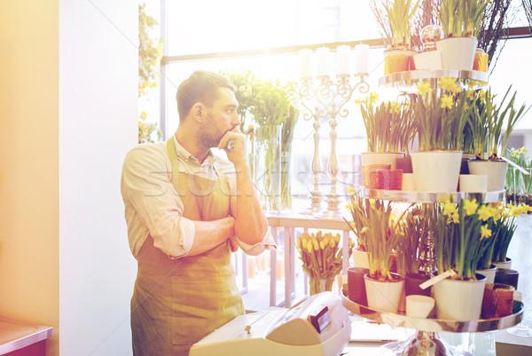 sad florist man or seller at flower shop counter Stock photo © dolgachov