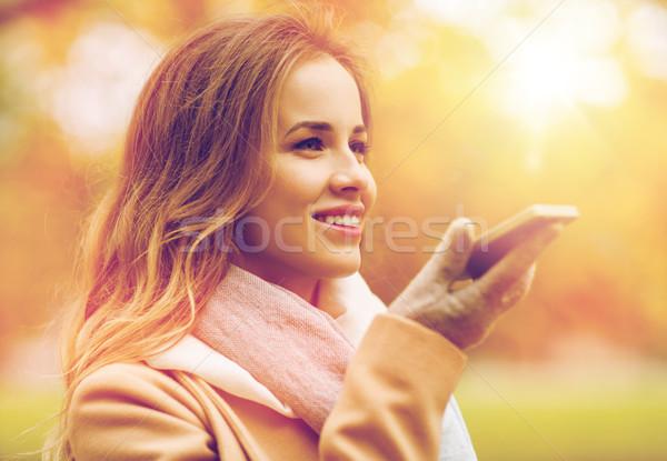 Kobieta głos smartphone jesienią parku sezon Zdjęcia stock © dolgachov