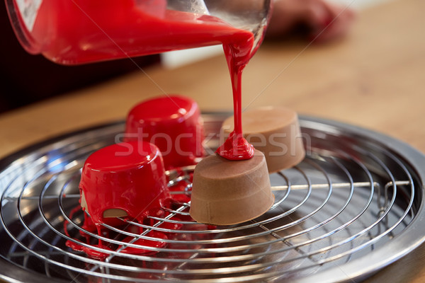 jug pouring glaze to cakes at pastry shop Stock photo © dolgachov