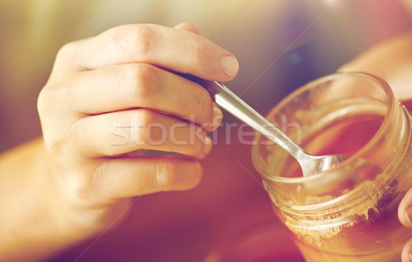 Donna mani miele cucchiaio cibo sano Foto d'archivio © dolgachov