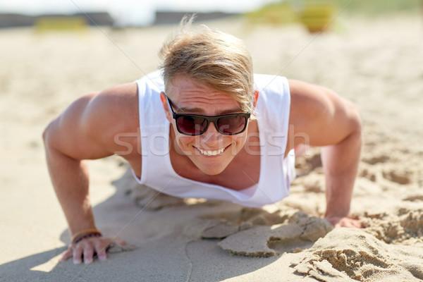 улыбаясь молодым человеком лет пляж спорт Сток-фото © dolgachov