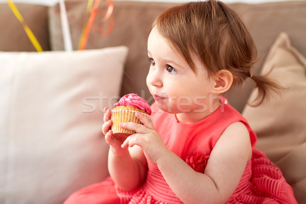 happy baby girl eating cupcake on birthday party Stock photo © dolgachov