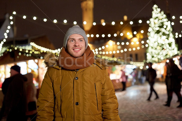 happy young man at christmas market in winter Stock photo © dolgachov