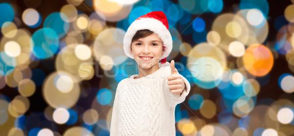 boy in santa hat showing thumbs up at christmas Stock photo © dolgachov