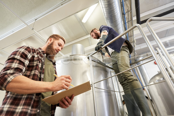 men with clipboard at brewery or beer plant kettle Stock photo © dolgachov
