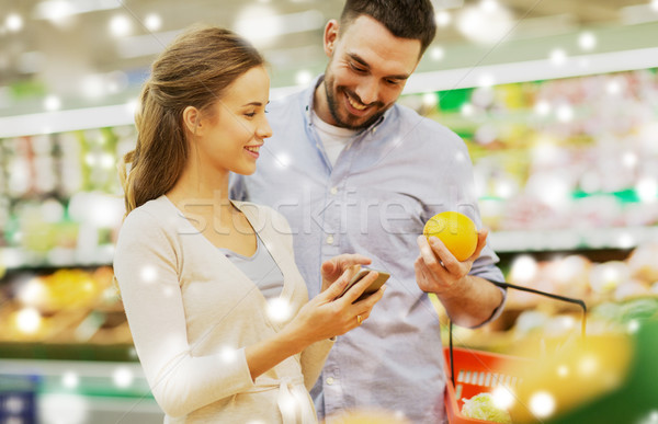 couple with smartphone buying oranges at grocery Stock photo © dolgachov